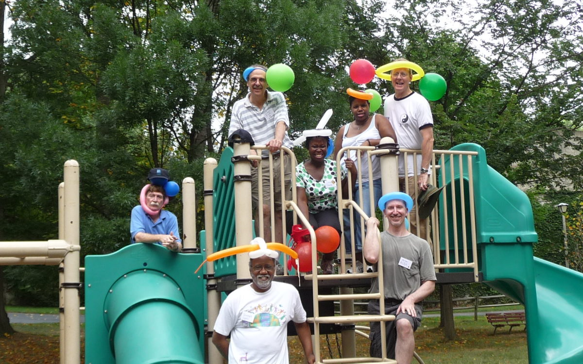 staff group with balloon hats on playground meant to depict value of joy and laughter