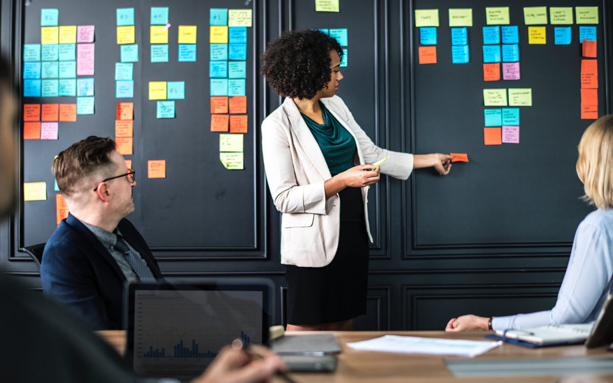 a facilitator moving sticky notes around a board in front of two participants during a meeting