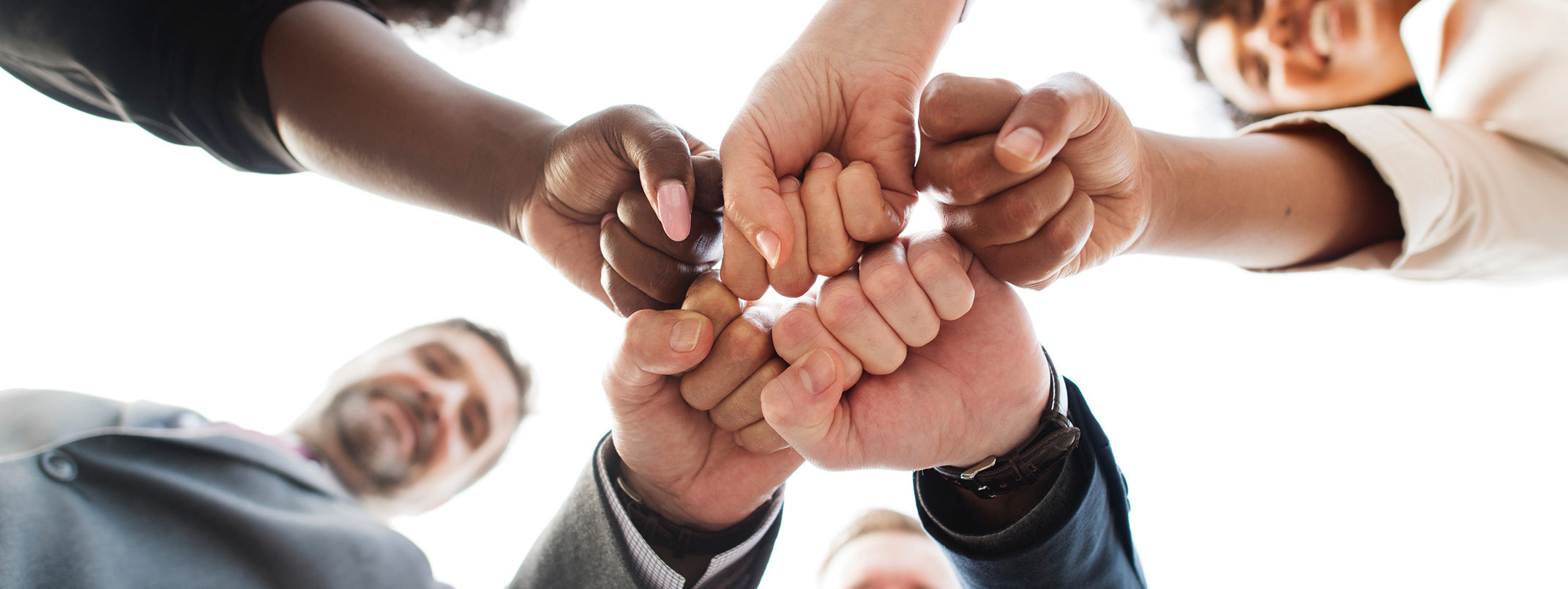 coworkers pounding hands in celebration to depict an empowering, unified, and supportive environment - view from below hands