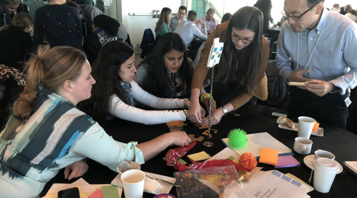 retreat participants in a group at a table doing a puzzle